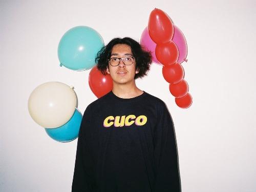 Cuco v mikině se svým jménem, za ním jsou balónky.
